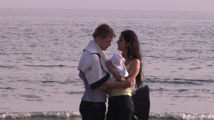 Young couple on the beach looking after their baby