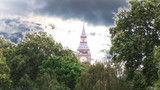 Big Ben surrounded by trees with moving clouds on background