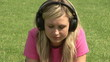 Woman listening music on the grass using headphones
