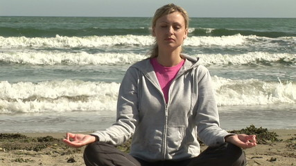 Young woman in sportswear doing yoga on the beach