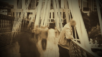 Man on a bridge with abstract people walking on the background