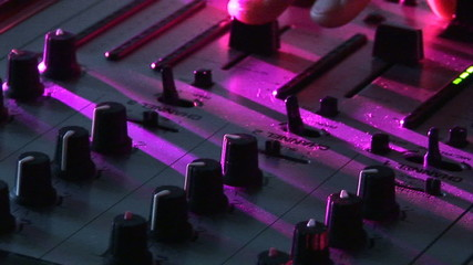 Close up of a dj using his mixer during an event