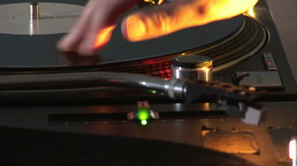 Close up of a dj scratching a disc on his mixer during a party