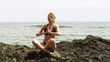 Young woman doing yoga sitting on rocks with ocean on background