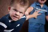 Fototapety Angry little boy glaring and fighting with his brother