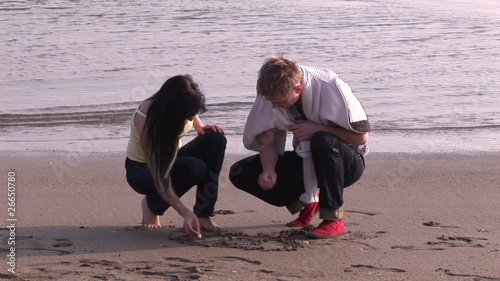 Lovely couple writing love message on the sand during honeymoon