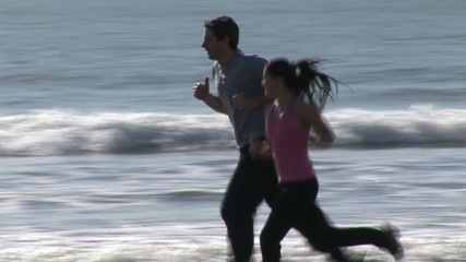 Sporty couple running by the sea