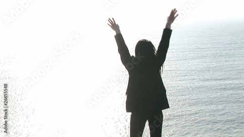 Rear view of a woman raising her arms in front of the ocean