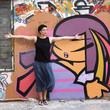Jeune femme s'étirant devant un mur couvert de graffitis