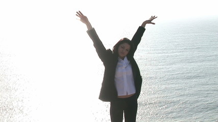 Woman raising her arms standing on the edge of a cliff