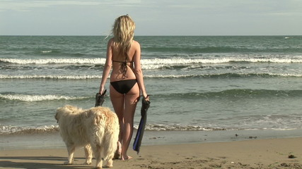 Attractive woman with her dog on the beach