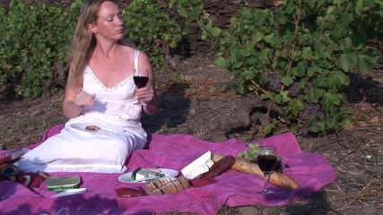 Woman eating pâté on toast in her vineyard