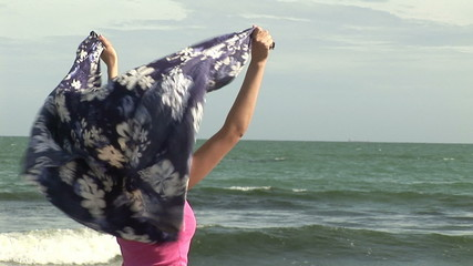 Woman holding her scarf on the wind