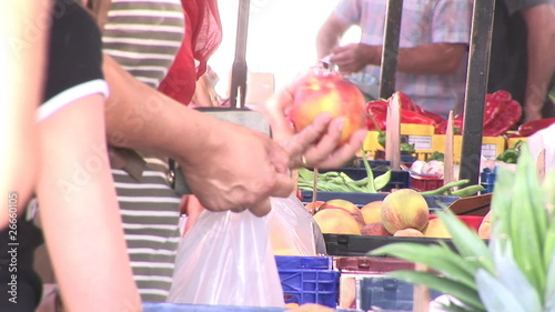 Close up of a customer putting apples in a plastic bag