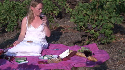 Woman drinking red wine while having pic nic in her vineyard