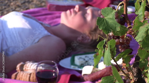 Woman tanning in a vineyard lying on the ground