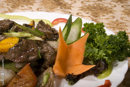 Fried juicy meat served with vegetables