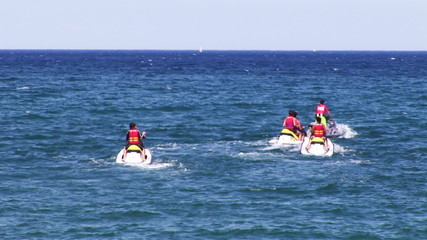 Group of friends doing some jetski in the sea during holidays
