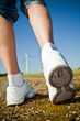Female hiker walking on a trail - wind turbines in the backgroun