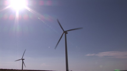 Below view of two wind turbines turning during a sunny day