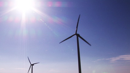 Below view of two wind turbines during a sunny day