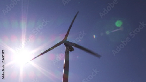 View of a wind turbine turning against beautiful blue sky