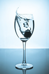 Splash of water and coins in a glass