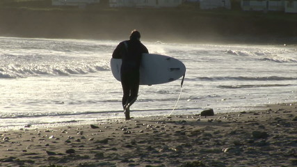 Surfer with his surfboard leaving the beach