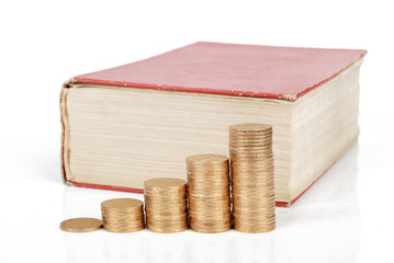 Coins with book on white background