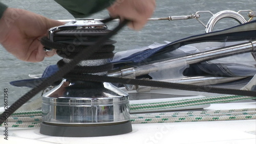 Close up of a man winding a rope in his boat