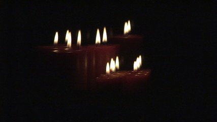 Scrolling up showing  lit candles in the dark