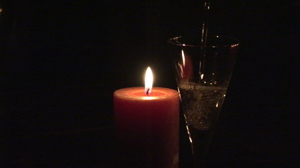 Candle with flute of champagne in the foreground