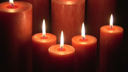 Scrolling showing eight lit candles in the dark