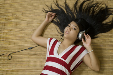 Asian woman laying down listening to music