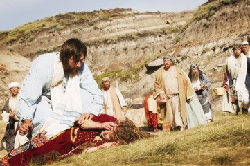 Crowd Watches As Jesus Helps Person Lying On Ground