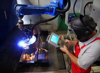 Schweisser bedient Roboter