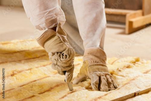 Mann schneidet Glaswolle zur Isolierung