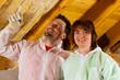 Paar bringt Dämmung an Dach an