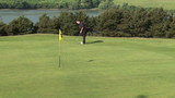 Golfer putting the ball in the last hole during competition