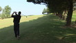 Rear view of a young man golfing