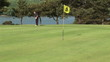 Happy golfer putting the ball in the fifth hole