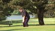 Golfer swinging on the green during a sunny day