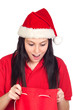 Surprised girl with Christmas hat looking on the sack