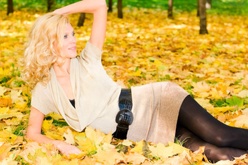 smiling young blonde woman on the autumn leaves