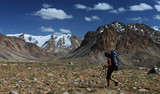 Hiker with backpack in mountains of Central Asia poster