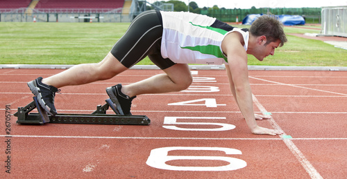Sprinter on the starting line putting feet  in starting block