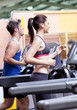Pretty woman with earphones using a treadmill with her boyfriend