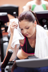 Exhausted woman wiping her face with a towel in sport centre