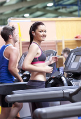Athletic woman listening to the music while using a treadmill