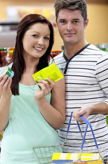 Portrait of a young couple buying cans standing in a groceryshop